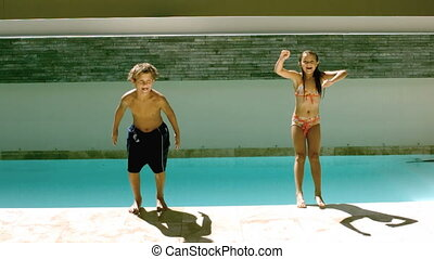 Siblings jumping together in the swimming pool in...
