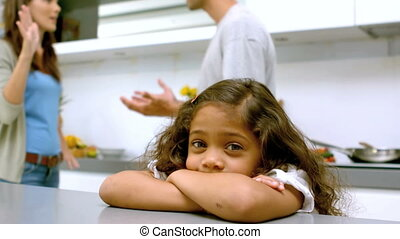 Sad girl with arms folded while parents quarreling in slow...