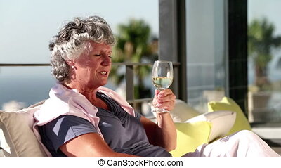 Mature woman enjoying glass of wine