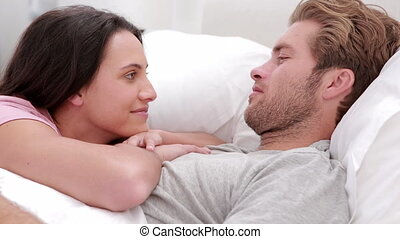 Couple talking in bed under the covers