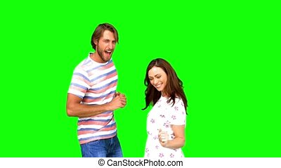 Two friends dancing together on green screen in slow motion