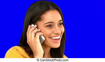 Woman talking on the phone on blue screen in slow motion