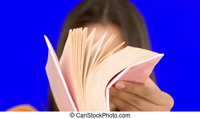 Woman flipping through a pink book on blue screen in slow...