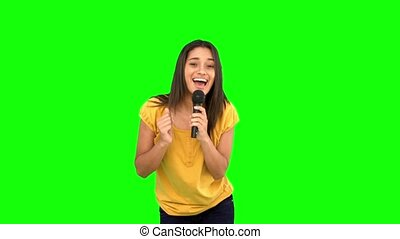 Woman singing and dancing on green screen in slow motion