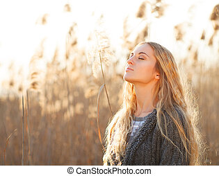 Portrait of a smiling blond woman relaxing outdoors in a...