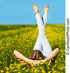 Young beautiful blond girl laying on the daisy flowers field...