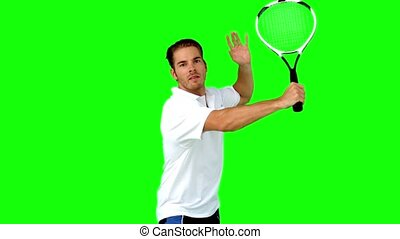 Man playing tennis in slow motion on green screen