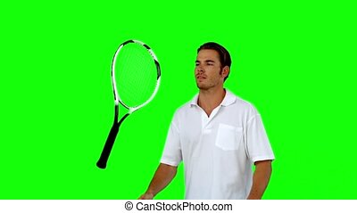 Tennis player throwing his racket in slow motion on green...