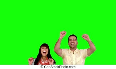 Two friends jumping on green screen in slow motion
