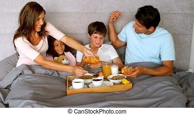 Family having breakfast in bed together in the bedroom in...