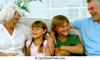 Children with grandparents on the couch in slow motion at...