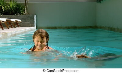 Siblings having fun in the swimming pool with a sunny day in...