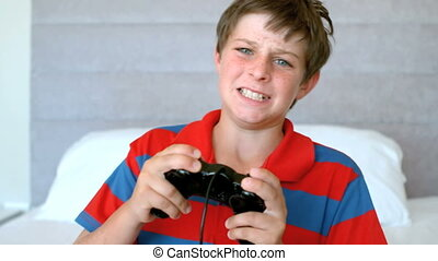 Concentrated young boy playing video games in slow motion at...