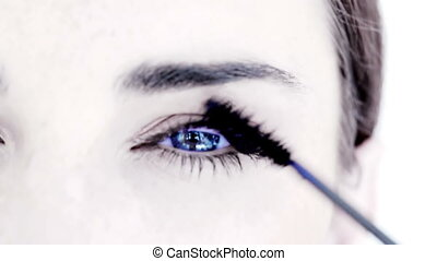 Woman making up her eye with mascara on white background