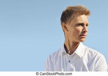 Handsome man - Handsome blond man on blue sky background at...