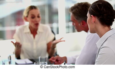 Angry businesswoman shouting at colleagues during a meeting
