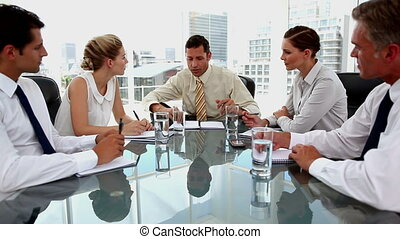 Businessman talking to colleagues taking notes in the office