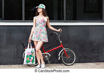 woman standing next to retro bicycle