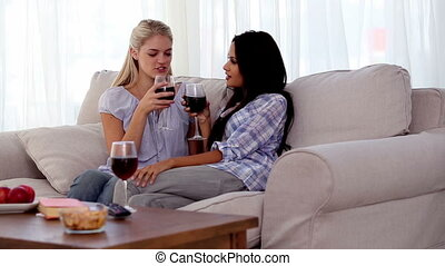 Attractive friends clinking their glasses of red wine...