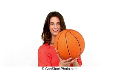 Woman having fun with a basket ball on white background in...