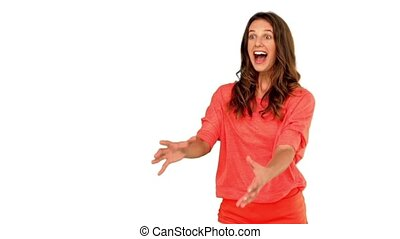 Cheerful woman catching a basketball on white background in...
