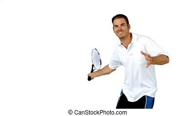 Young man playing tennis in slow motion on white background