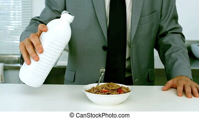 Businessman pouring milk into his cereals for his breakfast