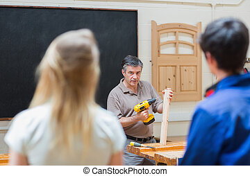 Teacher of a woodwork class teaching two students - Two...