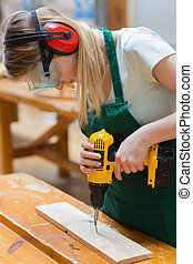 Student in a woodwork class using a drill - Student using...