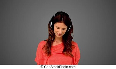 Woman listening to music on grey background in slow motion