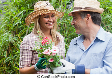 Man and woman holding a flower pot - Man and woman with hats...
