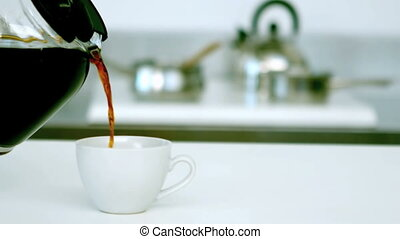 Black coffee being poured into cup of coffee in the kitchen