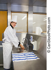 Smiling chef washing hands in the restaurant