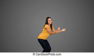 Woman jumping on grey background