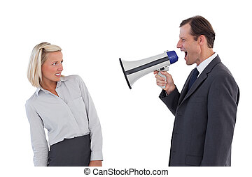 Businessman shouting at colleague with his megaphone on...