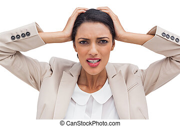 Young businesswoman holding her head between hands on white...