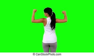 Woman in sportswear tensing her arms on green screen in slow...