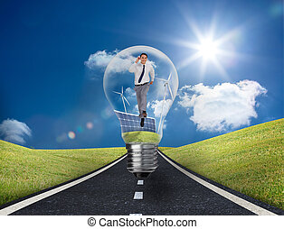 Businessman in light bulb with wind turbines and solar panels