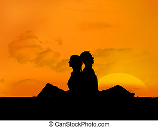 Silhouette of couple relaxing under a sunset