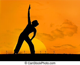 Calm silhouette of woman practicing yoga under sunset