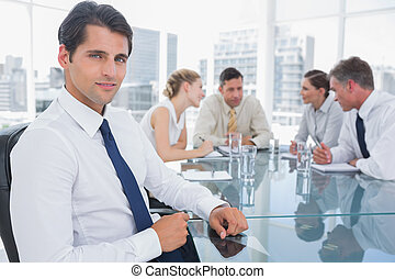 Portrait of a smiling businessman with colleagues working...