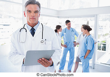 Serious doctor holding clipboard in front of his medical...