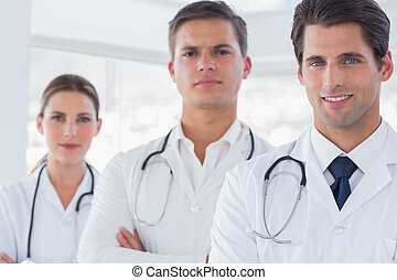 Three doctors with lab coats smiling to the camera