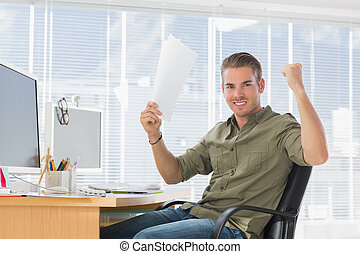 Creative business employee raising arms in a modern office