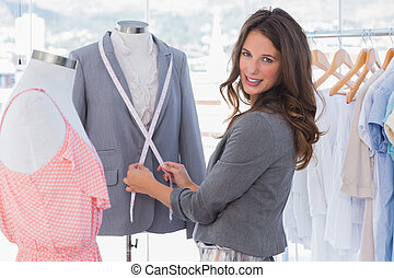 Attractive fashion designer measuring blazer and looking at...