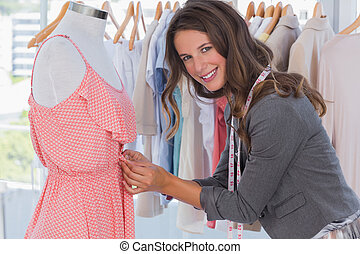 Attractive fashion designer picking needles in a dress