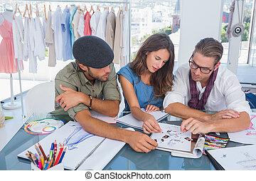 Three fashion designers working in - Three fashion designers...