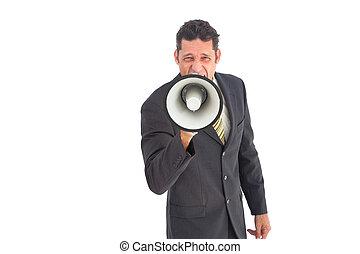 Businessman shouting into a megaphone wearing a suit