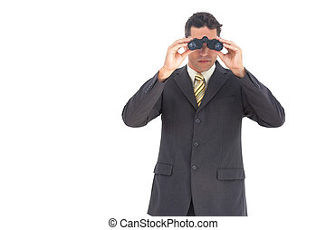 Businessman looking at the camera with binoculars