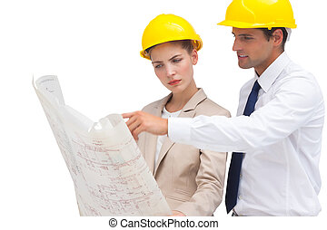 Serious architects looking at construction plan with yellow...